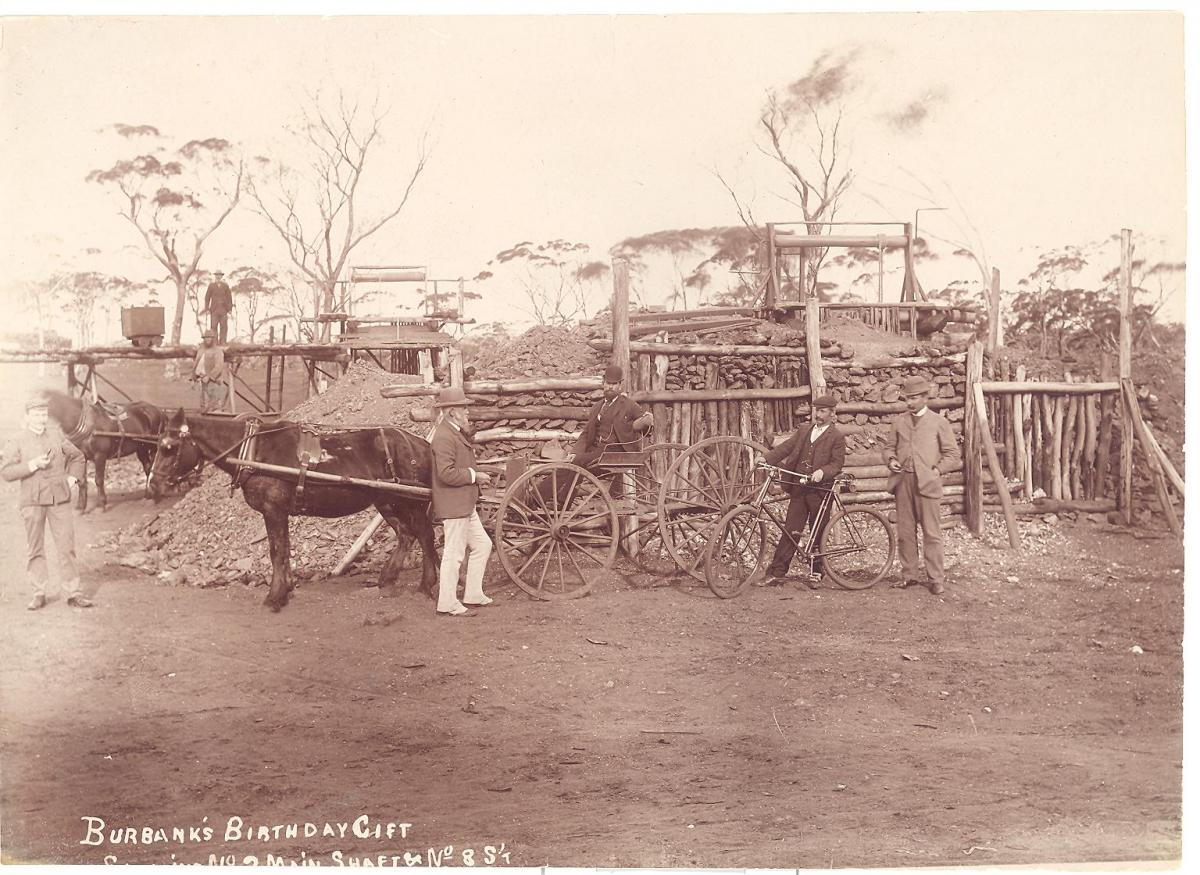 In front of a mine there is a man in a buggy in front of which is a man with a bicycle, another man standing beside the buggy and another beside the bicycle